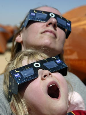 Australian girl and her mother watch the solar eclipse in the desert tourist camp in Galo, 1300 km south of the Libyan capital of Tripoli, March 29, 2006.