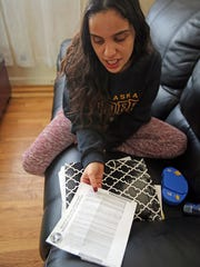 Ashlee Delgado looks at a bill she requested from the Thruway Authority for charges she owes at her home in Spring Valley, N.Y., on Feb. 8, 2018. Delgado's registration had been suspended over unpaid tolls on the Tappan Zee Bridge. To clear the suspension, she had to pay $1,548 - towing, storage, DMV fines, tickets, defensive driving class - and that didn't include the $3,500 in violations.