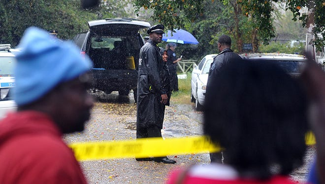 This 2013 photo shows spectators standing in the rain and watching as Jackson police officers investigate the scene of a multiple shooting.