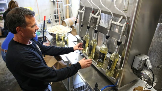 Tony Parnigoni bottles his Vignoles wine at Brianza Gardens and Winery in Verona on Thursday. Parnigoni has worked for four years to grow his vineyard and start the winery, and is celebrating a grand opening on Saturday, April 25.