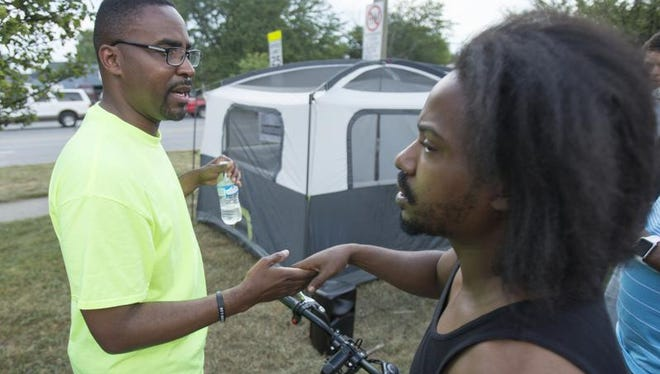 Pastor John Girton (left) greets well-wisher Dontay Adams on the first day of a month-long camping trip to raise awareness of city crime by sleeping in a tent for a month. The tent is at the corner of West 30th and Martin Luther King Jr. streets, Indianapolis, Friday, September 4, 2015.