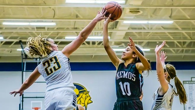 Shannon Twichell ,23, of Haslett blocks a shot attempt by Laya Hartman ,10, of Okemos during their game Friday December 4, 2015 in Haslett.