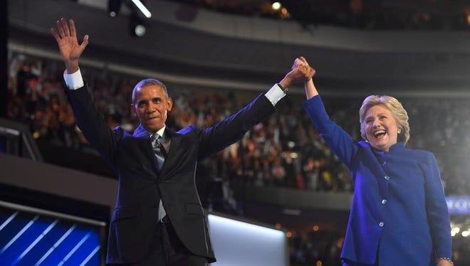 President Barack Obama and Hillary Clinton stand on stage after Obama spoke during the 2016 Democratic National Convention at Wells Fargo Center.
