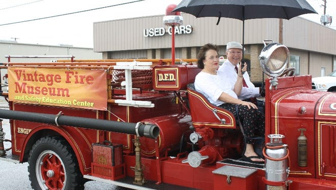 Angela Wiggins and Jim Keith lead the short fire truck parade through downtown Jeffersonville on Saturday as part of the Vintage Fire Museum's Bicentennial Muster Honoring George Wiggins, who died earlier this year.
