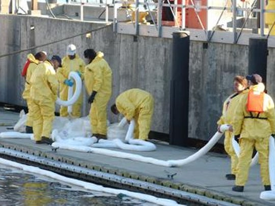 At the U.S. Coast Guard station in Philadelphia, cleanup workers lay out booms to help with the oil that was spilled by the tanker Athos 1 in November 2004.