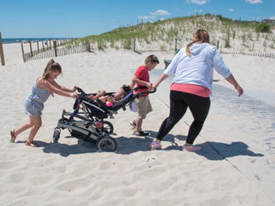 Erica Cirillo, Toms River, pulls her disabled child Leigha, 7, (in carriage) through the sand at the beach at F Street in Seaside Park. Her other children Kristianna, 8,  and Joey (red shirt), 7, assist. Jessica Krill (not pictured) of Toms River is on a crusade to make beaches more accessible for disabled people.