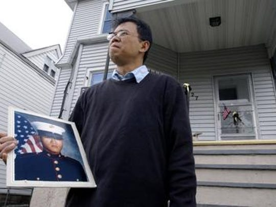 Cris Lagman (CQ) stands outside his family's home in Yonkers March 21, 2004 while holding a portrait of his brother Anthony Lagman, a U.S. serviceman who was killed in Afghanistan on the 18th of March, 2004