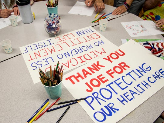 Signs of support for Sen. Joe Donnelly sit on a table