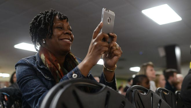 Taseline Rodgers takes a photo of her daughter Jasmine, who got an honorable mention in the poster and creative writing contest's K-3 age category at the 20th Annual Community Celebration of Dr. Martin Luther King Jr.'s Birthday at Northeast Wisconsin Technical College on Saturday.