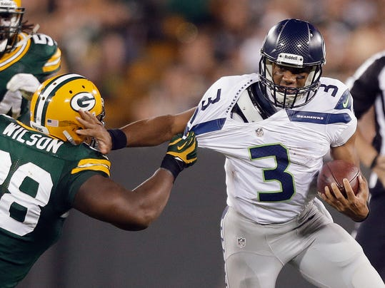 FILE - In this Aug. 23, 2013, file photo,k Seattle Seahawks quarterback Russell Wilson tries to get away from Green Bay Packers' C.J. Wilson during the second half of an NFL preseason football game in Green Bay, Wis. As Super Bowl champions, the Seahawks get to kick off the NFL's regular season by hosting the Packers on Sept. 4. That Thursday game is the first of four prime-time games on opening weekend. (AP Photo/Jeffrey Phelps, File)