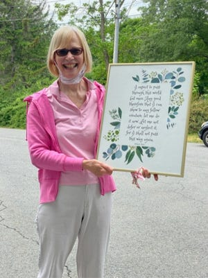Ingrid Wheeler, posing with a framed quote given to her by recent class participants.