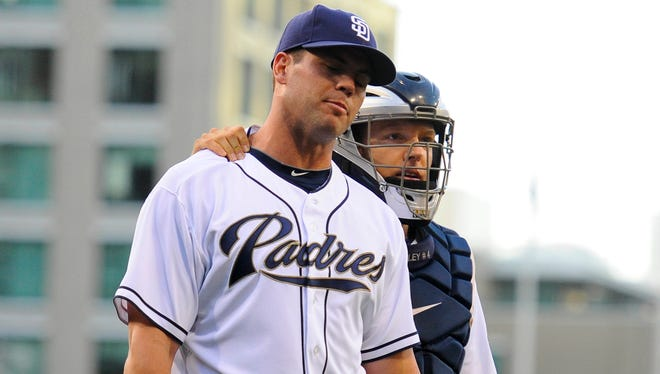 San Diego Padres starting pitcher Clayton Richard (33) walks off the field with catcher Nick Hundley (4) with an injury after two pitches during the first inning against the Los Angeles Dodgers at Petco Park.