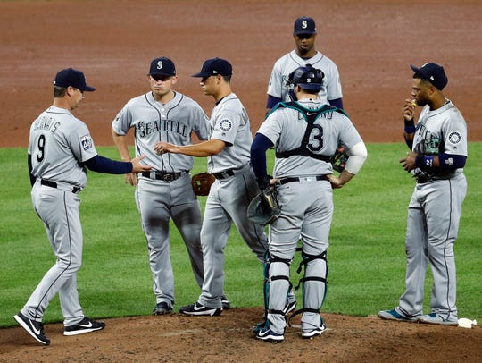 Seattle Mariners manager Scott Servais, left, relieves