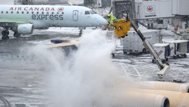 A plane is de-iced during a light snow at LaGuardia Airport in New York, Monday, Jan. 26, 2015. Airlines canceled thousands of flights into and out of East Coast airports as a major snowstorm packing up to three feet of snow barrels down on the region. (AP Photo/Seth Wenig)