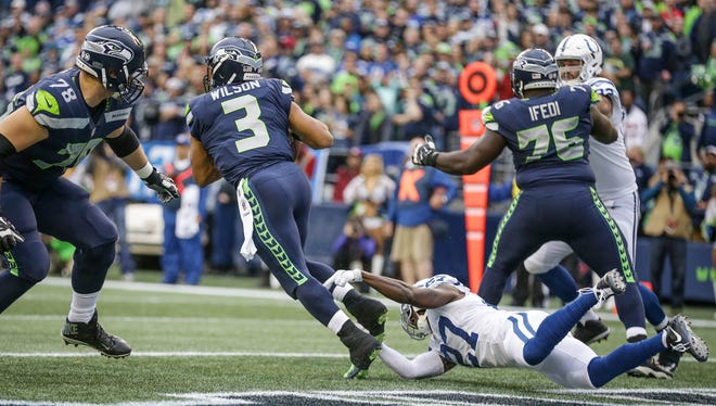Indianapolis Colts cornerback Nate Hairston (27) trips up Seattle Seahawks quarterback Russell Wilson (3) for the safety in the first quarter at CenturyLink Field in Seattle on Sunday, Oct. 1, 2017.