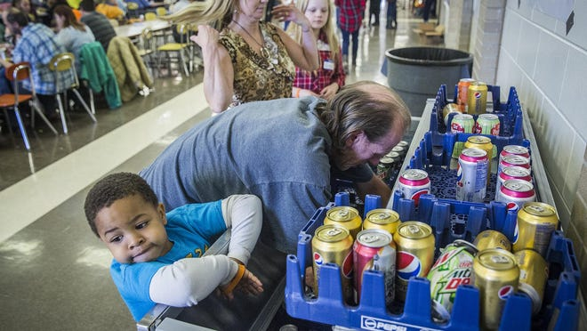 Attendees of Feed My Sheep grab drinks in Central's cafeteria after receiving a Thanksgiving day meal in this file photo