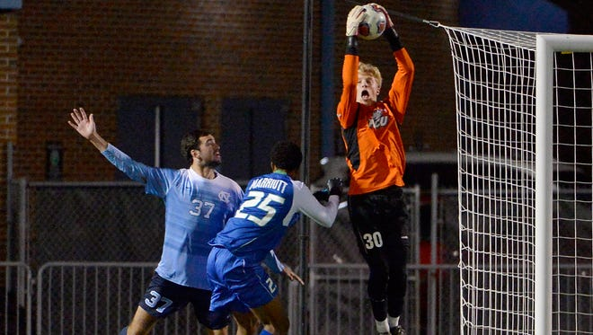 Florida Golf Coast goalie Jared Brown (30)  catches a goal kick over North Carolina Walker Hume (37) and Florida Golf Coast Kamar Marriott (25) during the second round of the NCAA men's soccer tournament on Fetzer Field at the University of Chapel Hill in Chapel Hill, N.C., Sunday, November 20, 2016. (Photo by Sara D. Davis for Naples Daily News)