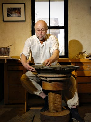 Richard Bresnahan, artist-in-residence at St. John's Pottery, works on a piece on the wheel in the studio in this file photo from April 7, 2010.