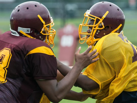 Two players perform a drill during practice at Washington