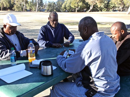 A group of friends play dominoes outside the James O. Jessie Desert Highland Unity Center in Palm Springs on Tuesday, Jan. 12, 2015.