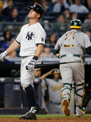 New York Yankees left fielder Brett Gardner, left, reacts after an eighth-inning strikeout in which he stranded two runners on base in Yankees' 7-3 loss to the Oakland Athletics in a baseball game in New York, Thursday, April 21, 2016. Oakland catcher Stephen Vogt heads to the dugout.