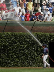 """FILE - In this July 26, 2008 photo, Chicago Cubs pitcher Ryan Dempster hoses down a St. Louis Cardinals fan holding a """"The Curse Lives"""" sign in the bleachers at Wrigley Field before a baseball game between the Cubs and Cardinals in Chicago.  The Abraham Lincoln Presidential Museum plans to unveil an exhibit chronicling the history of the rivalry between the Chicago Cubs and the St. Louis Cardinals."""
