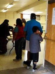Voters check in on Tuesday at the Naschitti Chapter House.