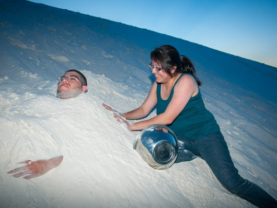 Noe Gutierrez is buried in the sand by Maria Barillas at White Sands National Monument. Full Moon Nights this summer feature concerts and guided hikes.