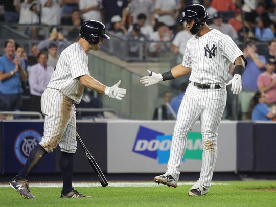 New York Yankees second baseman Gleyber Torres (25) is congratulated at home plate by left fielder Brett Gardner (11) after hitting a home run in the fifth inning against the Washington Nationals at Yankee Stadium.