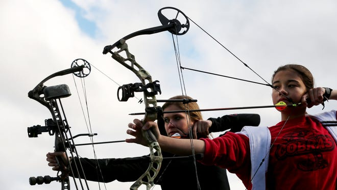 Samantha Sorokti , 14, who got her first doe while bow hunting in 2013, and Kayla Bartkowski,  13, who started bow hunting this year, practice as Steve Vanzile teaches youth bow hunting and archery.