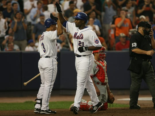 Carlos Delgado is greeted after crossing home by Damion