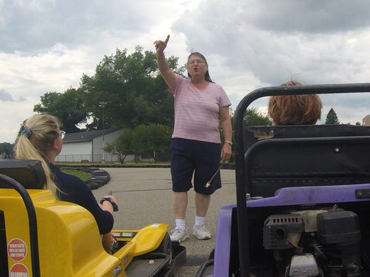 Judy Heppler, co-owner of Riverview Recreation, gives instructions to go-kart racers.