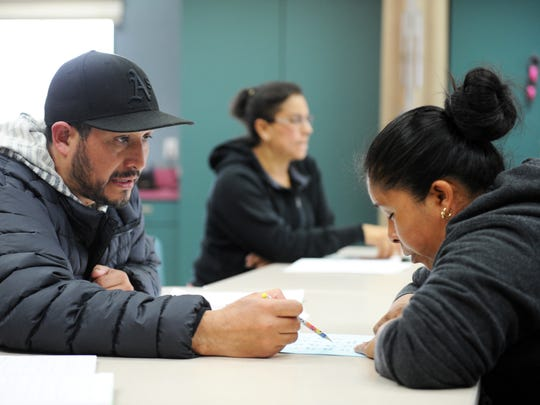 JosŽé Lopez helps out fellow student Alberta Rodriguez with an exercise in Jaimee DePompeo's adult school ESL class at the Alisal Family Resource Center in Salinas.