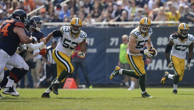 Green Bay Packers linebacker Clay Matthews (52) runs with the ball after making an interception off a tipped ball in the third quarter during Sunday's game against the Chicago Bears at Soldier Field in Chicago.