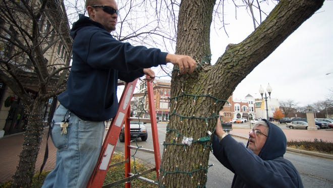 Volunteers from Reid Health help hang new lights in trees along East Main Street in downtown Richmond, Ind. on Tuesday, Nov. 29, 2016.