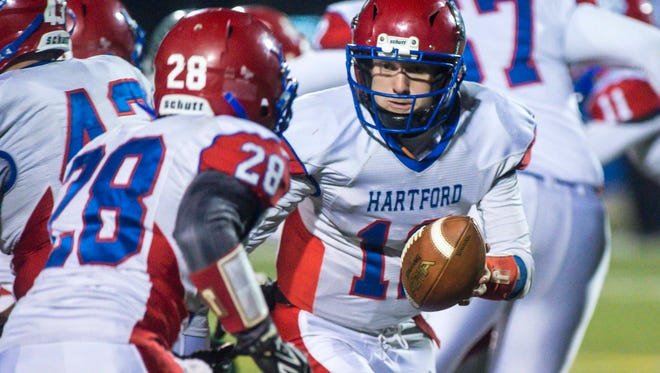 Hartford's TylerHamilton, right, hands off to Kody Rhodes against St. Johnsbury in the Division 1 high school football state championship in Rutland on Saturday, November 11, 2017.