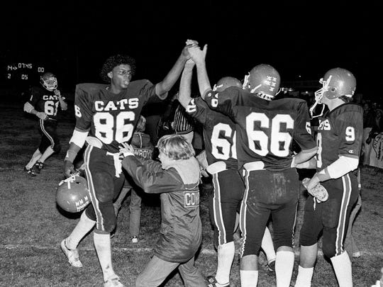 Overton High tight end Richard Bradley (86) high-fives a couple of his teammates on the sideline after making a play against Father Ryan High at home Oct. 30, 1981.