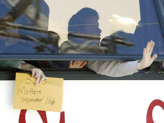 A Fundamentalist Church of Jesus Christ of Latter-Day Saints woman hangs a sign out of the bus on April 24, 2008, as the women are moved from the San Angelo Fairgrounds. About 260 children remained in the coliseum, but all mothers were removed.