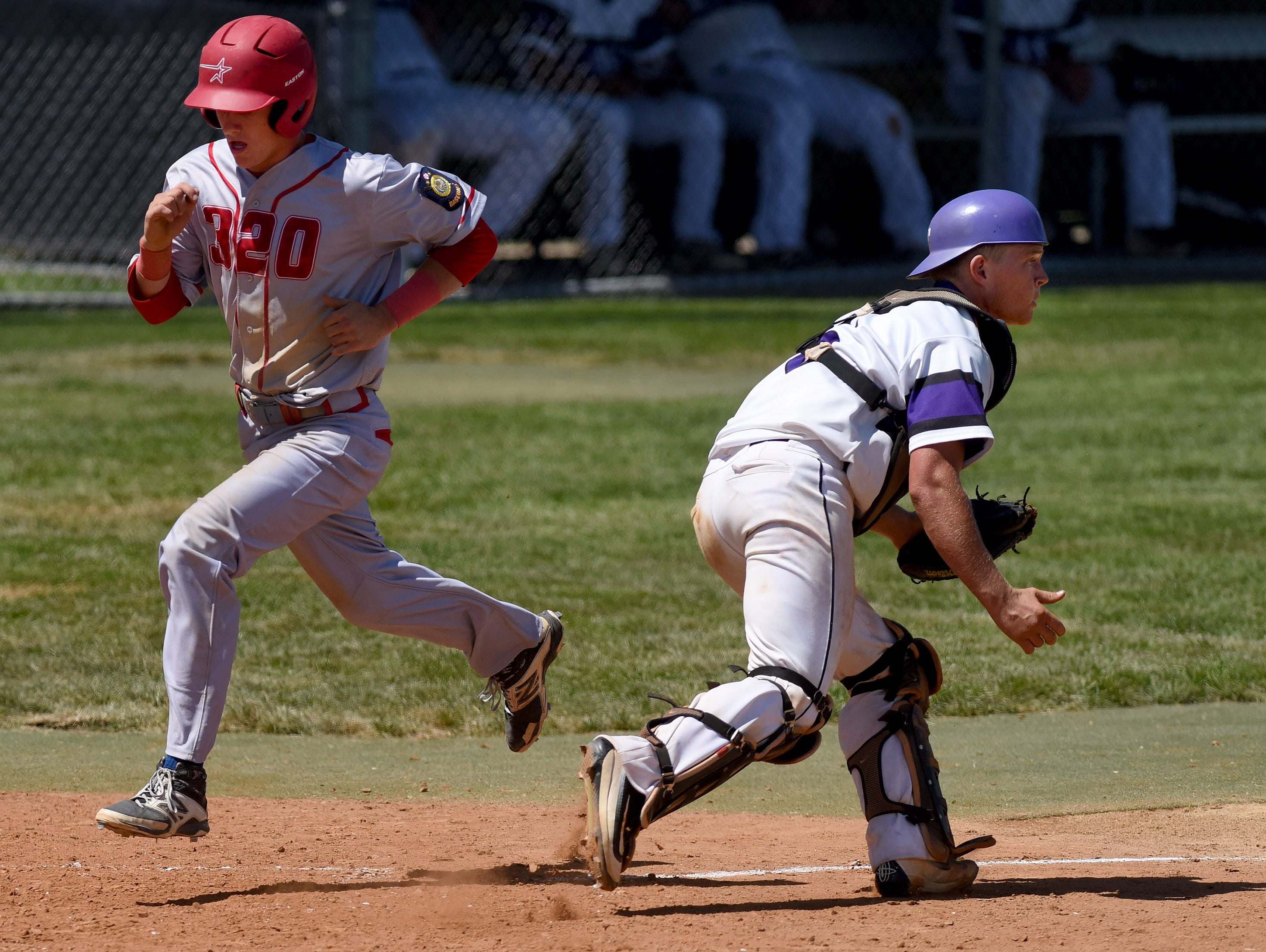 Rapid City Post 320's Cam White runs home past Sioux Falls East Post 15's catcher Josh Nevin during the American Legion Class A Baseball State Tournament at Harmodon Park on Saturday afternoon.