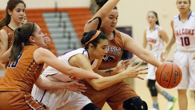 Eastlake's Jessica Espinoza, center, fights for the ball with Charlize Bustillos, left, and Sabrina Minjarez of Riverside Friday night at Eastlake. The Rangers outshot the Falcons 50-44.