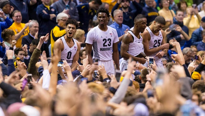 Golden Eagles players celebrate with fans after defeating Villanova.