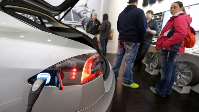 Customers check out a new Tesla all electric car, Monday, March 17, 2014, at a Tesla showroom inside the Kenwood Towne Centre in Cincinnati