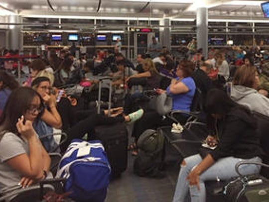 Passengers jam the Delta Air Lines boarding area at