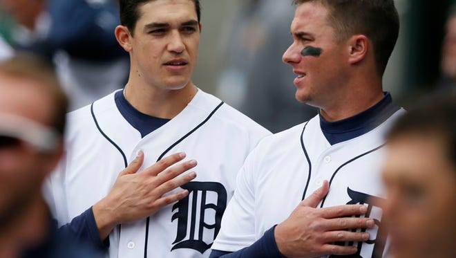 Detroit Tigers starting pitcher Kyle Lobstein, left,  talks with catcher James McCann as they stand through America The Beautful for the seventh inning stretch.