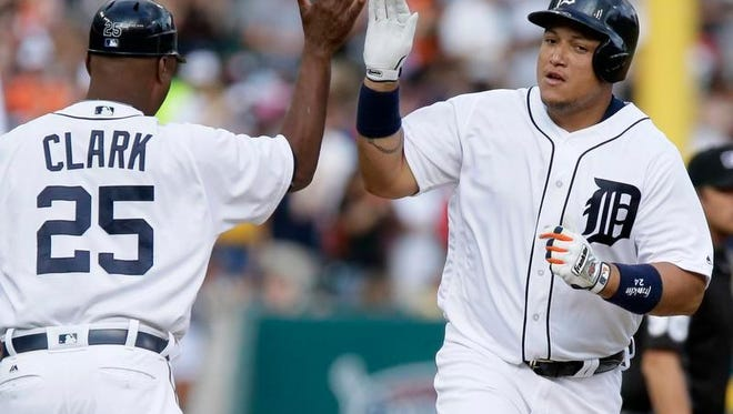 Miguel Cabrera of the Tigers is congratulated by third base coach Dave Clark after hitting a solo home run against the Mariners during the first inning at Comerica Park.