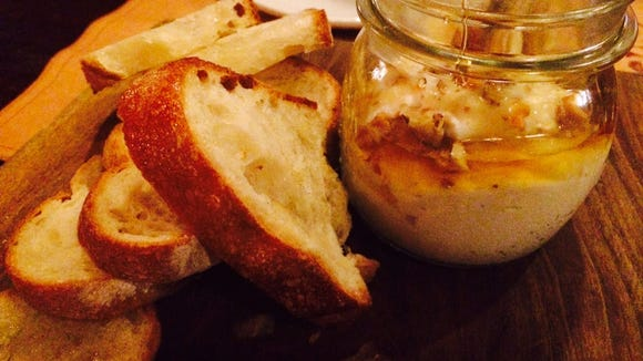 A jar filled with fresh ricotta and honey and walnuts