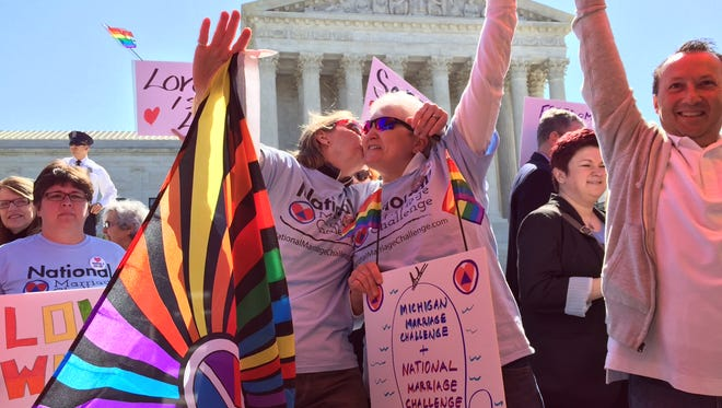 Glenna DeJong, 54, left and her wife Marsha Caspar, 53, kiss in front of the U.S. Supreme Court as they gather to show support with the National Marriage Challenge Tuesday Apr. 28, 2015.