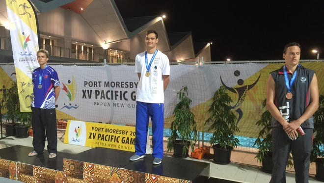 Guam's Benjamin Schulte stands on the podium wearing a gold medal for winning the 400-meter individual medley July 7 at the Pacific Games in Port Moresby, Papua New Guinea.
