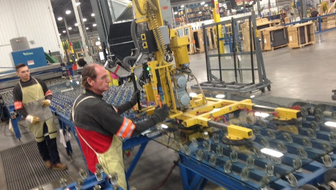 Employees at Viracon work to improve glass panes during a tour with the Utah Manufacturers Association May 6, 2015.