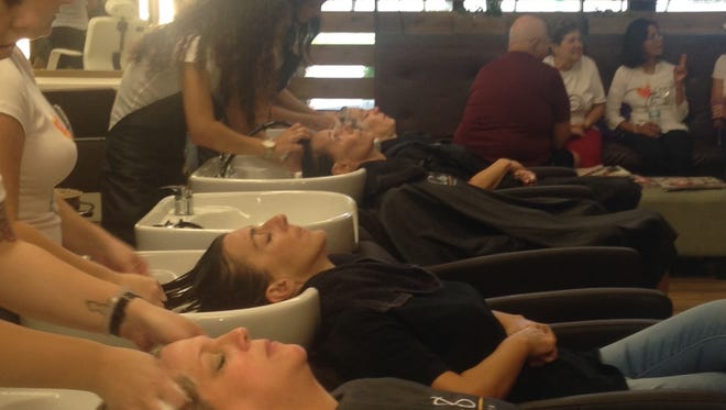 Nelly Truax, seated far right, talks during a fundraising event for her at Cre8 Salon & Spa in Cape Coral on Sunday. The salon donated all proceeds for all services to Truax's cancer treatment bills.